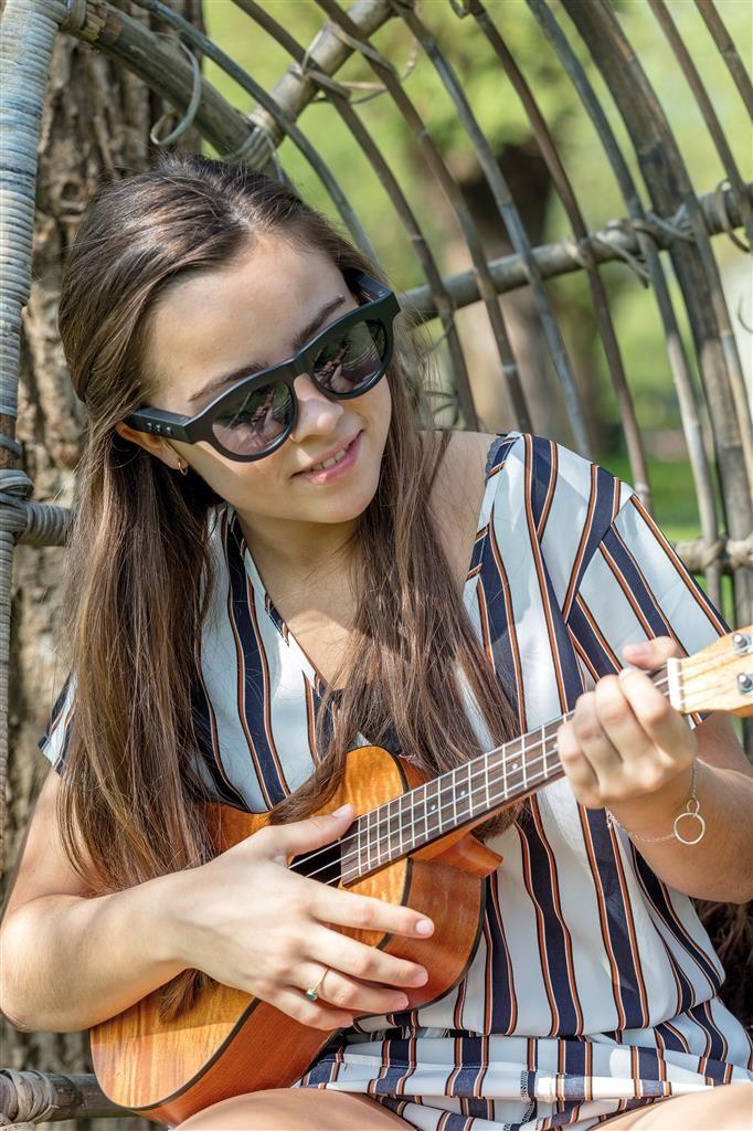 Ragazza che suona la chitarra mentre indossa occhiali con speaker