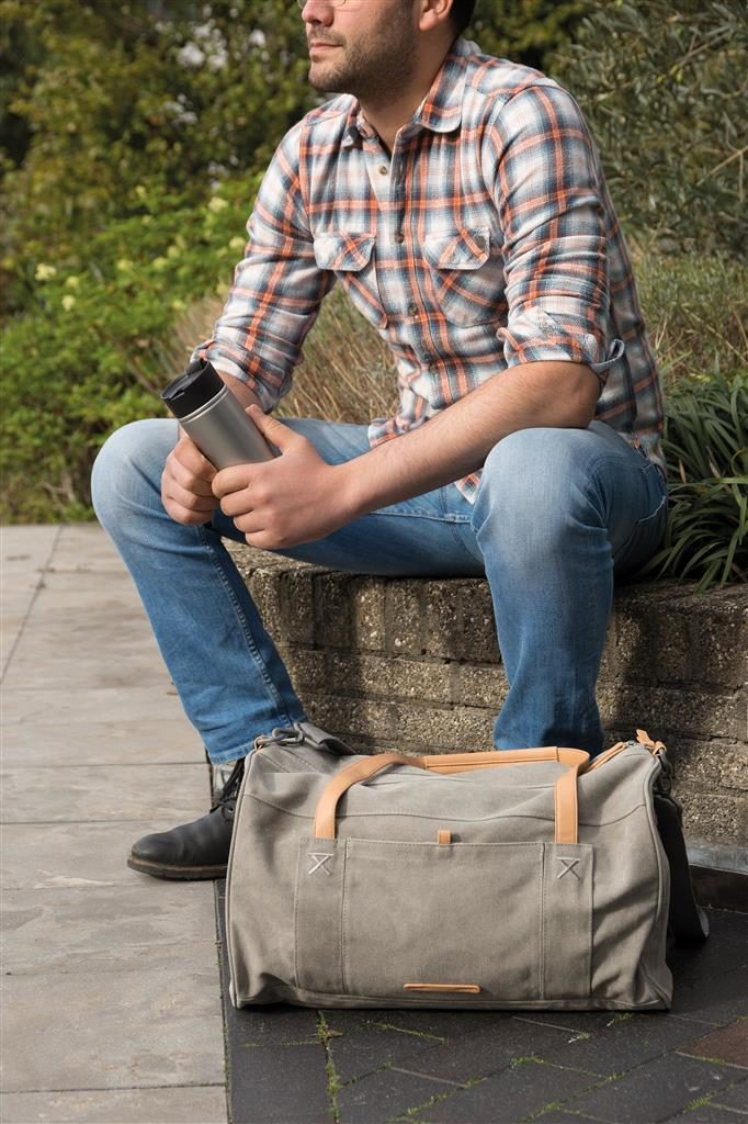 Uomo con borsa ecologica e borraccia in mano