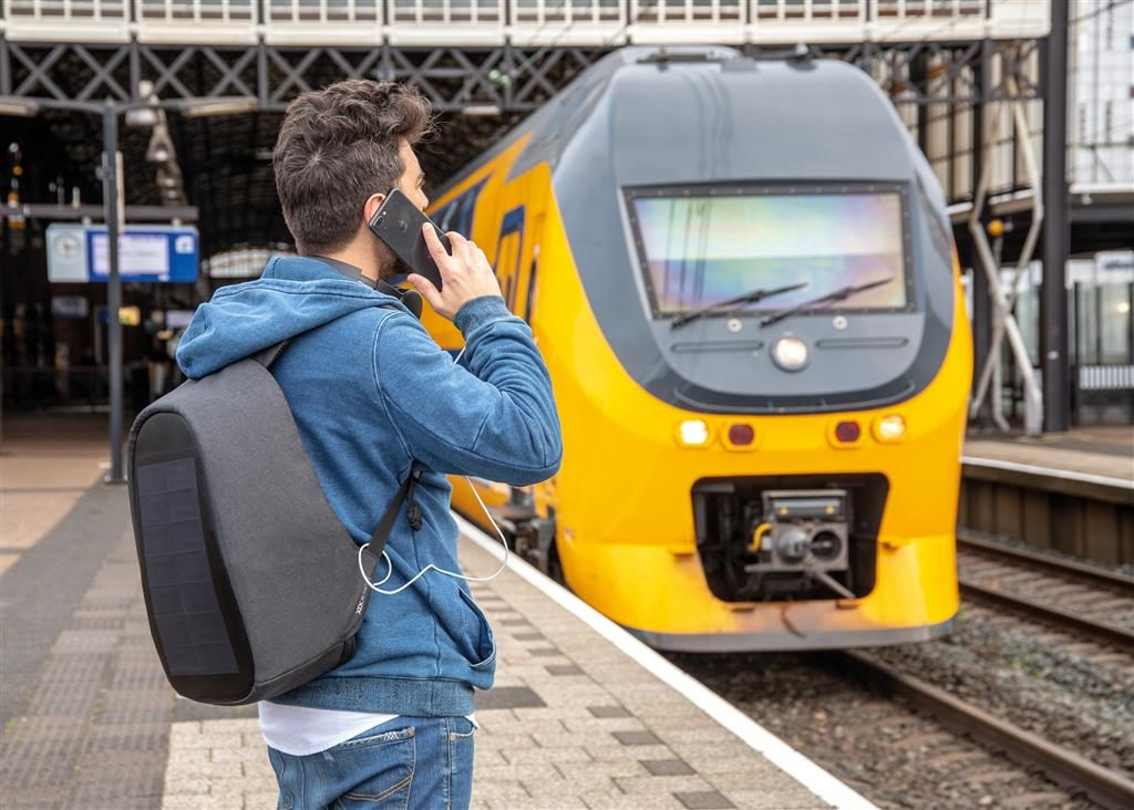Uomo in stazione con zaino e smartphone