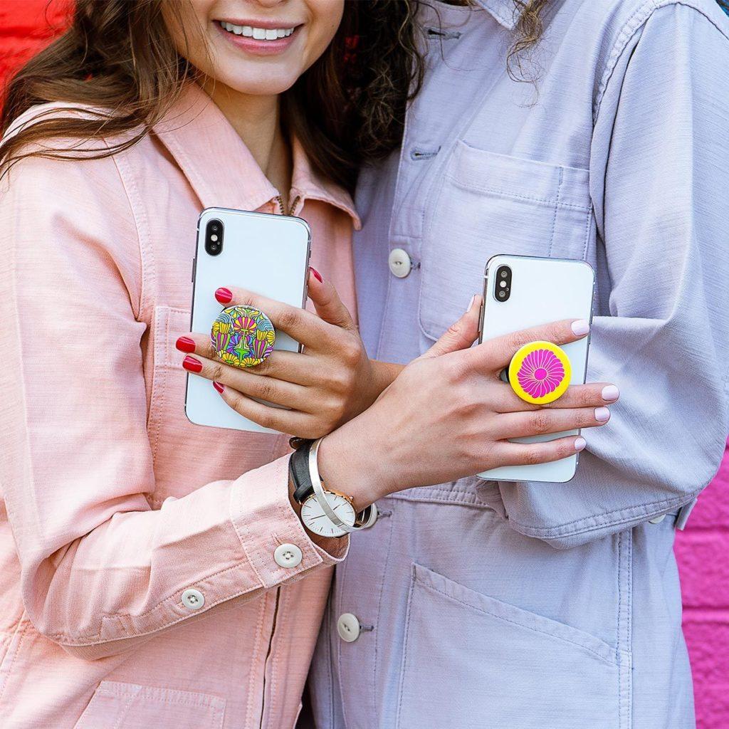 due ragazze con smartphone e supporto personalizzato, gadget economico