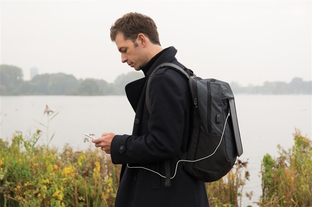 Uomo con zaino solare e smartphone