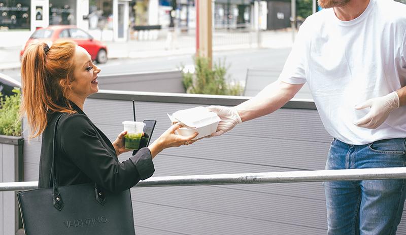 ragazzo che consegna il pranzo take away a una ragazza