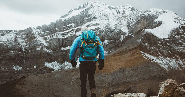 ragazzo che scala una montagna come esepio di attività outdoor