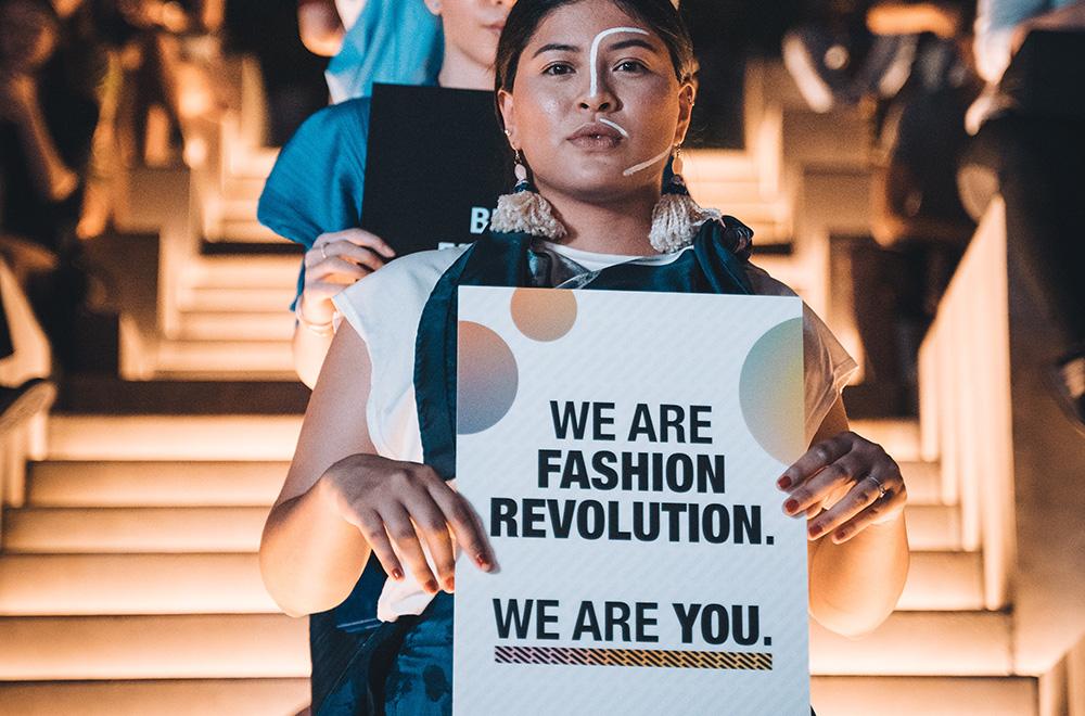 ragazza che manifesta per la fashion revolution con cartello in mano