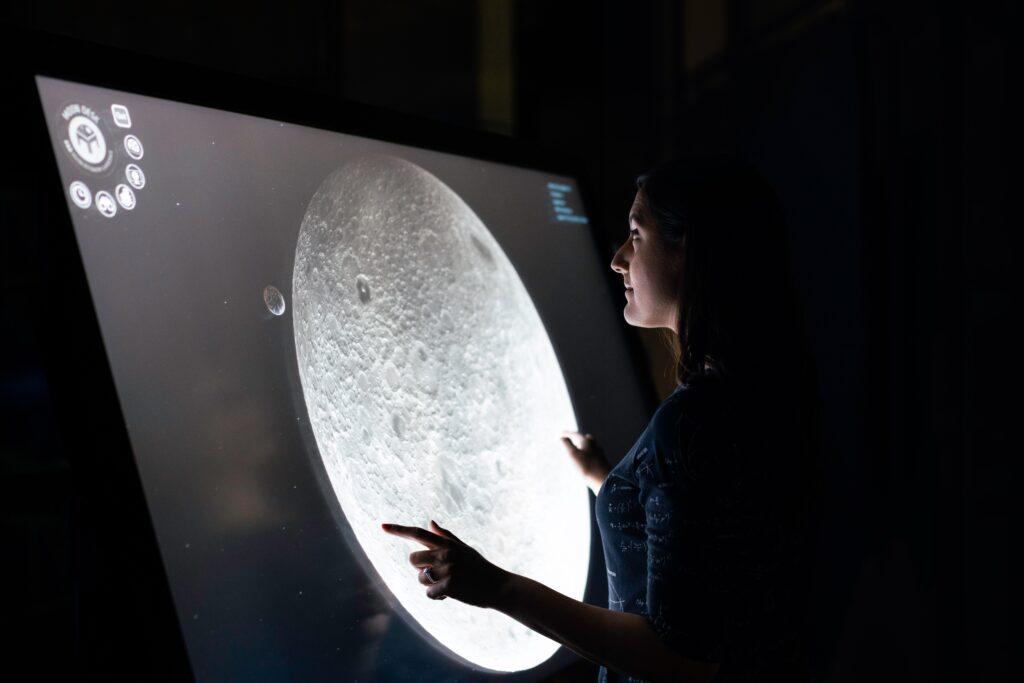 ragazza che interagisce con schermo in un museo come esempio di mostre virtuali