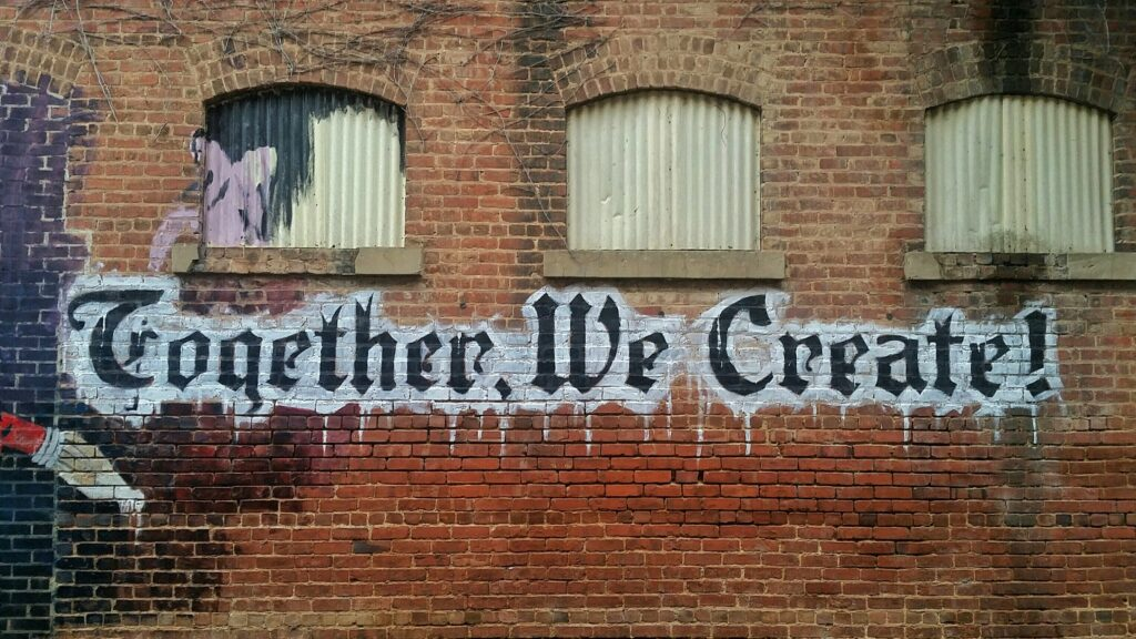 murales con scritta together we create, il motto adatto alla raccolta fondi