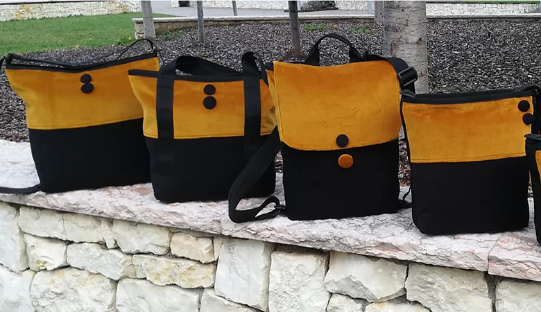 4 borse ideate dalla sartoria creativa gialle e nere su un muretto