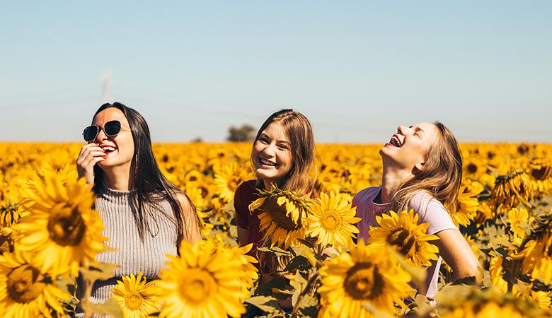 tre ragazze che sorridono in un campo di girasole