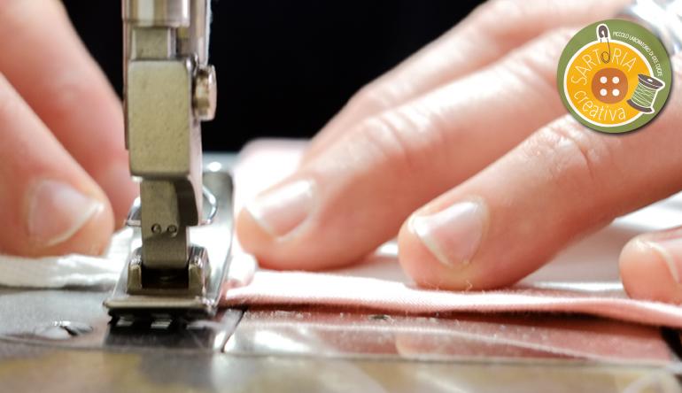 foto della sartoria creativa con mani e macchina da cucire in primo piano