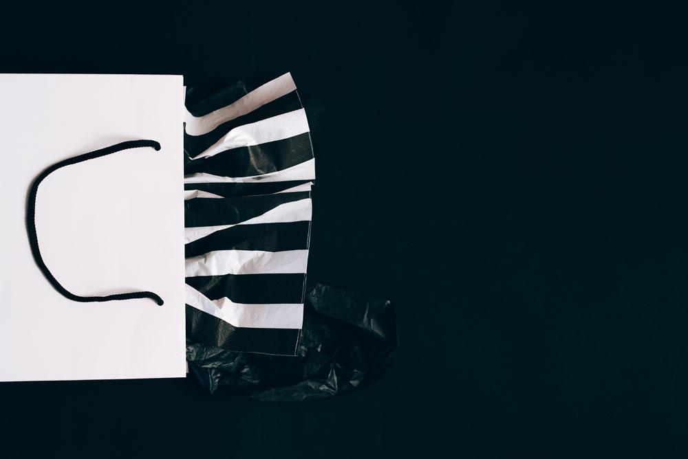 sacchetto bianco su sfondo nero con carta a righe