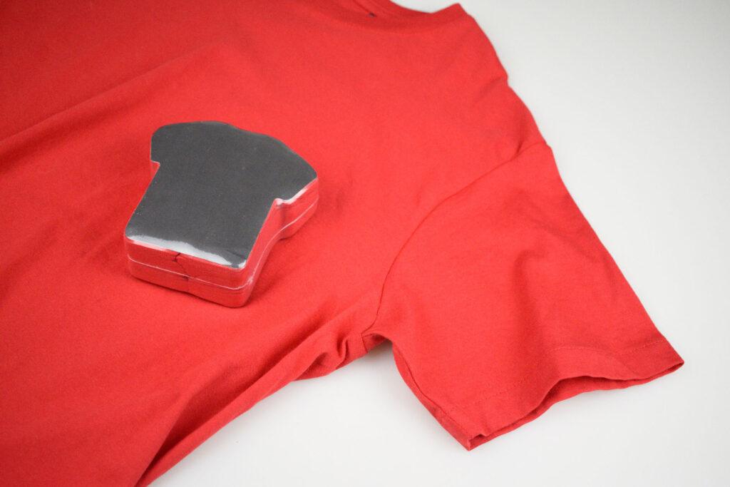maglietta rossa compressa in un packaging a forma di maglietta
