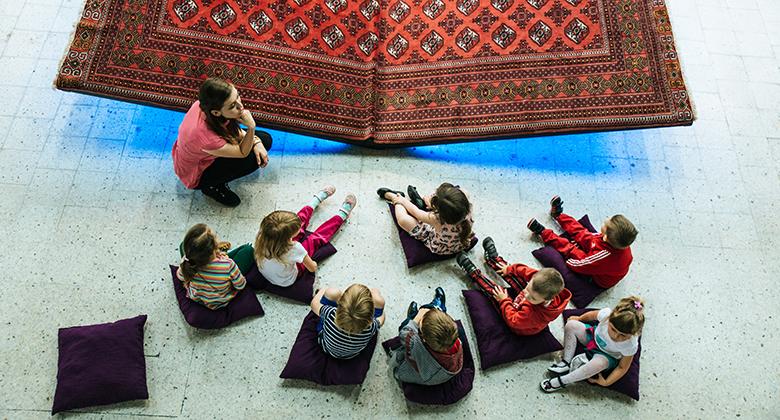 bambini con maestra seduti davanti a un grande libro durante un camp di estate al museo