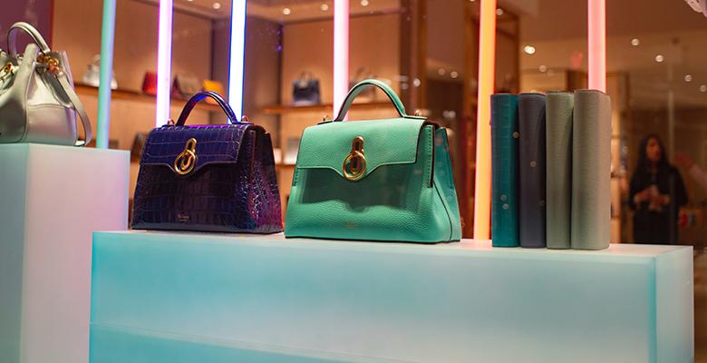 borsa viola e verde acqua in vetrina come esempio di accessorio che coniuga moda e arte