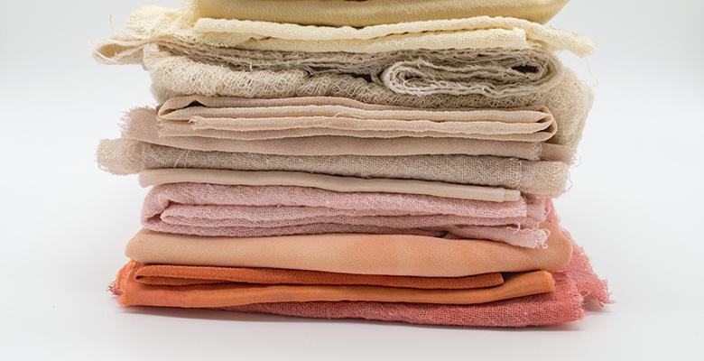 tessuti colorati impilati uno sull'altro in gradazione dall'arancione al panna
