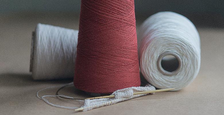 rocchetti di cotone bianco e rosso come esempio di tessuto sostenibile